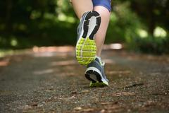 Woman jogging away from camera Stock Photos