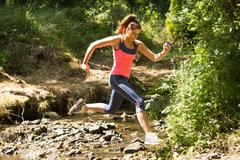 Sporty young woman leaping over a stream Stock Photos
