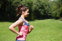 Fit woman running in the sunshine and smiling - stock photo
