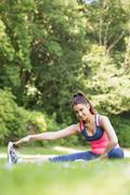 Stock Photo of Sporty woman stretching her leg and smiling at camera