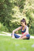 Stock Photo of Young fit woman sitting on the ground