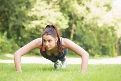 Stock Photo of Serious fit woman doing plank position