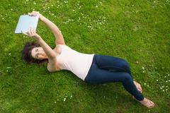 Stock Photo of Happy young woman lying on a lawn using her tablet