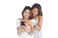 Stock Photo of Two young sisters using smartphone