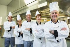 Team of chefs smiling at the camera - stock photo