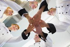 Chefs joining hands in a circle Stock Photos