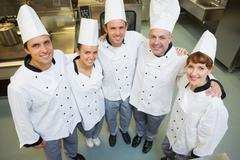 Stock Photo of Five happy chefs smiling up at the camera
