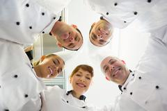 Five smiling chefs standing in a circle Stock Photos