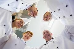 Stock Photo of Five chefs standing in a circle