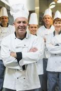 Five chefs wearing uniforms while posing in a kitchen - stock photo