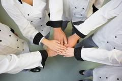 Five chefs joining hands in a circle Stock Photos
