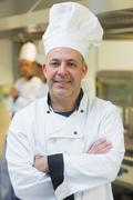 Proud mature chef posing in a kitchen - stock photo