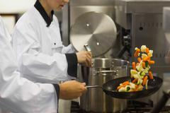 Two chefs working in a busy kitchen Stock Photos