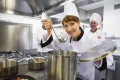 Stock Photo of Young female chef tasting a soup