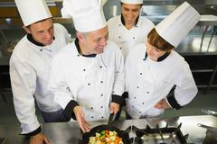 Stock Photo of Experienced head chef showing pan to his colleagues