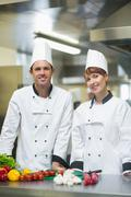 Two young chefs posing in a kitchen Stock Photos