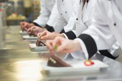 Stock Photo of Team of chefs garnishing dessert plates