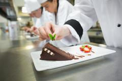 Close up of chef putting mint leaf on chocolate cake - stock photo