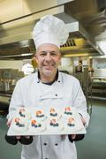 Mature chef presenting proudly plate of meringues Stock Photos