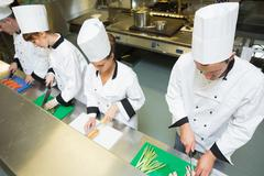 Stock Photo of Four chefs preparing food at counter