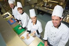 Stock Photo of Four chefs preparing food at counter smiling at camea