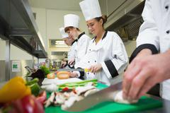 Four chefs preparing food at counter in a row - stock photo