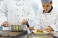 Young female chef finishing a plate - stock photo
