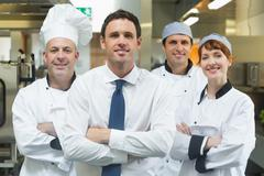 Restaurant manager standing in front of team of chefs Stock Photos