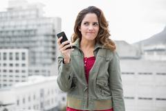 Skeptic gorgeous brunette in winter fashion holding smartphone Stock Photos