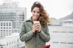 Smiling gorgeous brunette in winter fashion holding disposable cup Stock Photos