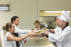 Two cooks handing plates to servers Stock Photos