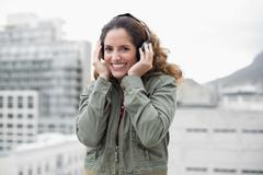 Happy gorgeous brunette in winter fashion listening to music Stock Photos