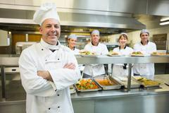 Proud mature head chef posing in a modern kitchen - stock photo