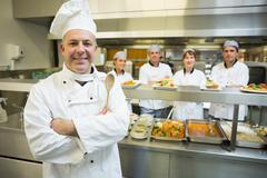 Experienced head chef posing proudly in a modern kitchen - stock photo