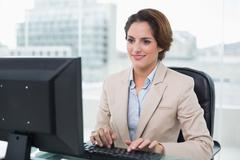 Smiling businesswoman sitting in front of computer - stock photo