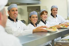 Young chefs presenting some plates to the head chef Stock Photos