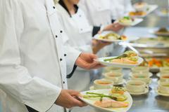 Stock Photo of Chef holding salmon dishes