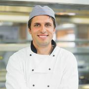 Handsome young chef smiling at camera - stock photo