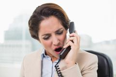 Outraged businesswoman shouting into phone Stock Photos