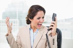 Outraged businesswoman shouting at phone Stock Photos