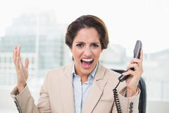Furious businesswoman looking at camera and holding phone Stock Photos