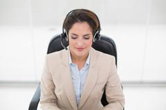 Happy call center agent sitting in swivel chair Stock Photos
