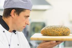 Young baker inspecting a seeded loaf of bread - stock photo