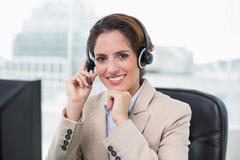 Stock Photo of Content businesswoman touching headset