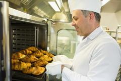 Mature baker putting some croissants into an oven - stock photo