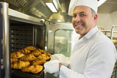 Mature baker smiling proudly at the camera - stock photo