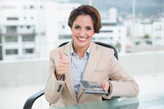 Stock Photo of Smiling businesswoman holding calculator and giving thumb up