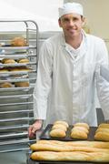 Young male baker standing in a kitchen - stock photo