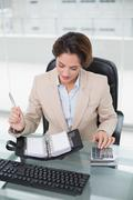 Stock Photo of Businesswoman using calculator and looking at diary