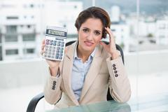 Worried businesswoman holding calculator Stock Photos